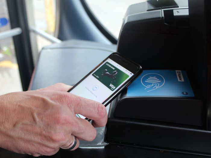 Photo of a customer using Apple Pay on a Damory or Tourist bus